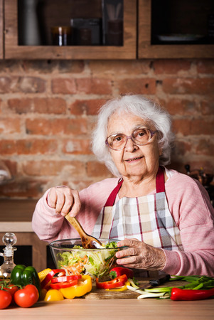 Senior woman cooking vegetable salad at the kitchen at home
