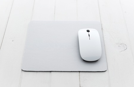 White wireless mouse on a mouse pad 스톡 콘텐츠