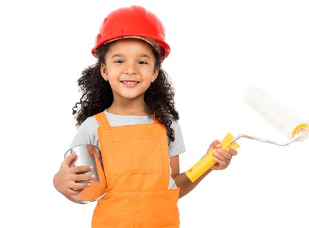 Little girl-worker in orange uniform with paint and roller in hands isolated on a white