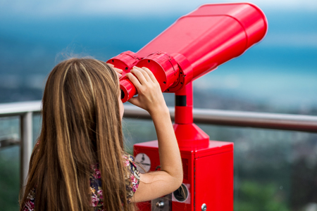 Young girl using a tower viewer to look at panoram of city