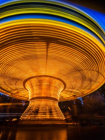 Abstract long exposure of bright rotating merry go carousel at night Stock Photo