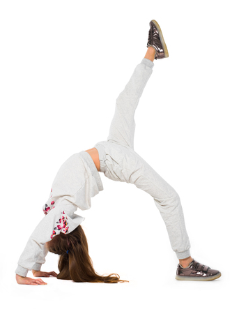 Young girl doing bridge position on the one leg support, one leg extended upwards 写真素材