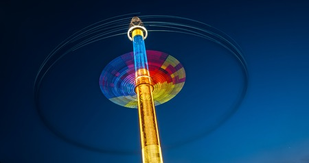 Abstract blurred multicolour spinning high speed carousel in front of dark night sky in amusement park