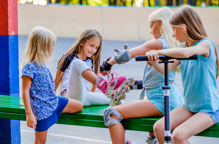 Children with kick scooter and roller-states sitting on the green bench