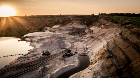 Aerial view of sandy quarry surface and mine equipment near lake at evening sunset