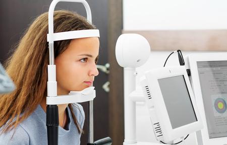 Teenage girl udergoing eye survey on modern diagnostics device in ophthalmologic clinic Stock Photo