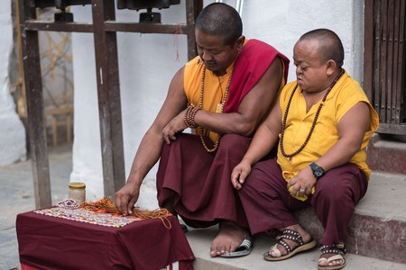 Kathmandu, Nepal - 06 October 2017: Two tibetian monks in traditional costumes sold some stuff at Boudhanath Stupa in Kathmandu, Nepal Sajtókép