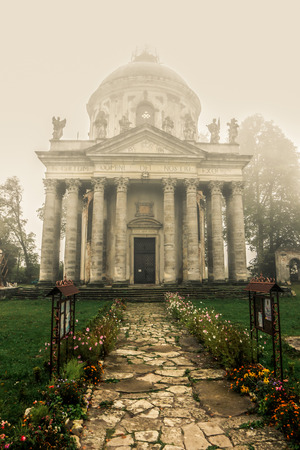 Misty view of Roman Catholic church Exaltation of the Holy and St. Joseph near Pidhirtsi village, Lviv, Ukraine. Old church in couryside at dawn