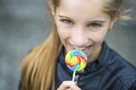 Beautiful little girl with candy, outdoor 写真素材
