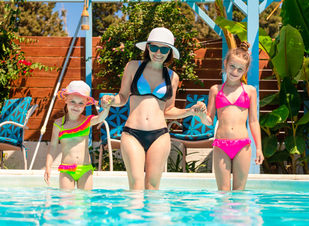 Smiling mom with little daughters stand by holding hands and going to swim in the sunshine blue pool 스톡 콘텐츠