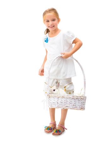 Little smiling blond girl holding white basket with white rabbit isolated on white background Standard-Bild