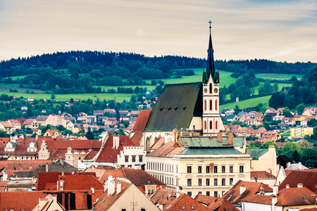 Top view of old architecture of Cesky Krumlov on the background of green forest hills