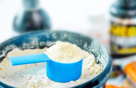 Nahaufnahme blaue Maßschale im Eimer gefüllt mit Sportproteinpulver