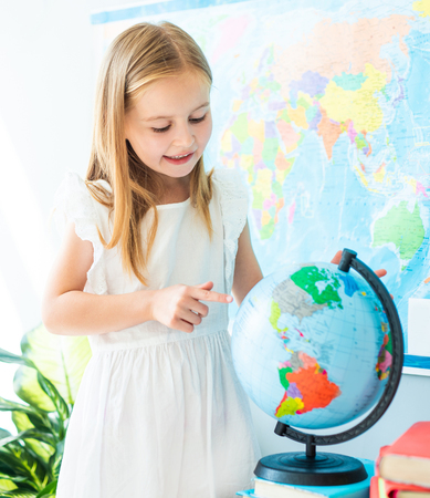 Cute little schoolage girl look pointing on the globe in the sunshine classroom