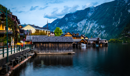 Evening scenery of lake and wooden buildings at the berth on the background of mountains in Hallstatt, Austria Foto de archivo - 116573629