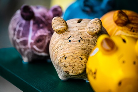 Colorful ceramic pig shape copycats on the wooden shelf