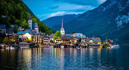Sunshine evening scenery of beautiful Hallstatt at the wide lake on the background of rocky forested mountains Stockfoto