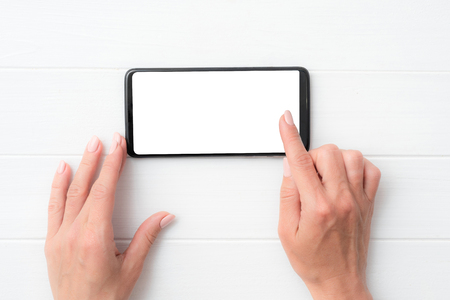 Mock up of user hands with black smartphone on white table for your design
