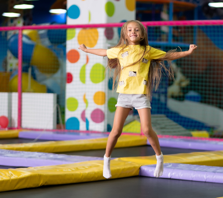 Little excited girl in a yellow T shirt jumping on the trampoline on the colorful amusement park background