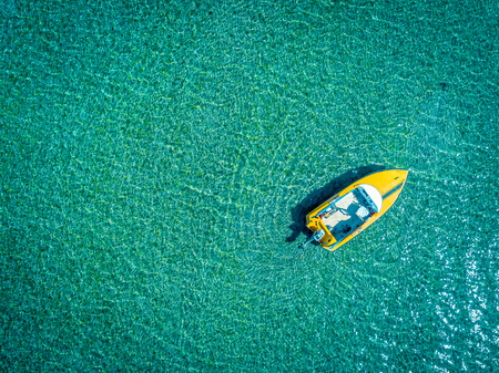 Aerial view of alone boat sailling on turquoise water Reklamní fotografie