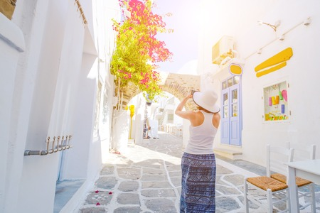 Woman in white hat walking the narrow street of the old city of Naoussa, Paros island, Greece. Girl taking photo of beautiful architecture