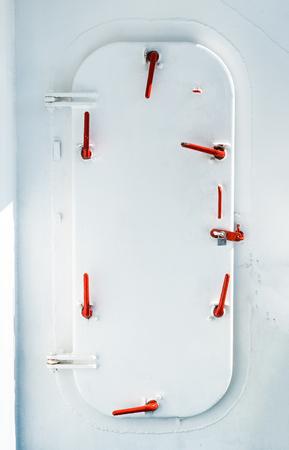 White watertight ship door with red door handles
