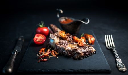 Roasted piece of beef on the bone with vegetables and cutlery on vintage background