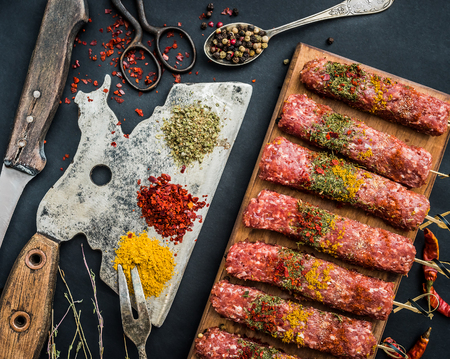 Raw kebab with spices and old kitchen ax on a black table