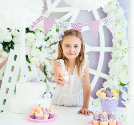 Pretty smiling little girl holding tasty cake in the beautiful decorated candy bar