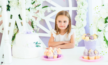 Pretty little smiling girl standing at the white table with cakes in the beatiful decorated candy bar