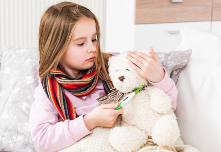 Little ill girl with scarf measuring teddy bears temperature 版權商用圖片
