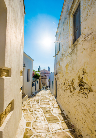 Typically rustic narrow paved passage between ancient stone walls on midday in Lefkes, Greece