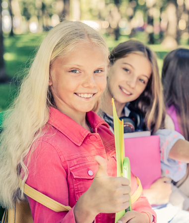 Smiling schoolgirl with thumbs up sit together in the park