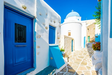 Wide-angle shot of the traditional greek street with white houses and blue doors and windows on streets of Lefkes, Paros island, Greece