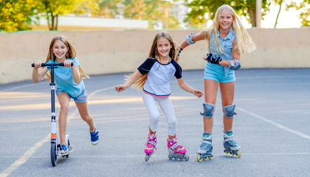 Pretty smiling little girls compete riding in the skatepark at warm summer evening