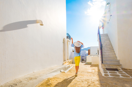 Beautiful little girl in white hat relax on a typical street in Greece