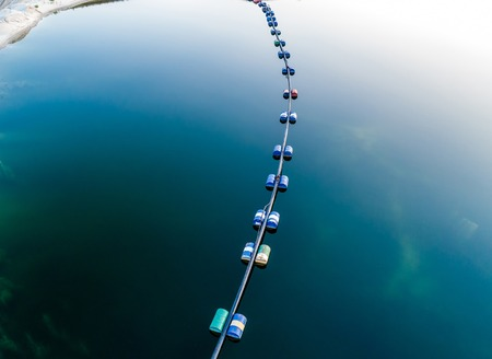 Aerial view of blue tube with barrels on the deep navy blue lake