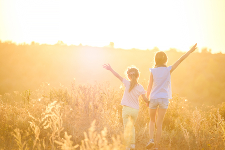 Little girls stand by holding hands looking on sunshine evening field with joyfully raised hands Stock Photo