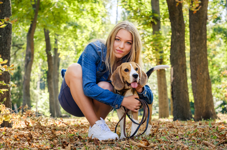 Pretty blond girl sit hugging beagle dog in a sunshine autumn park