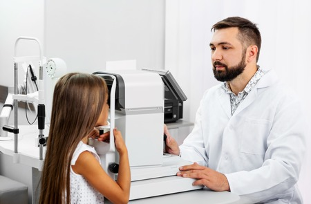 Little blond girl undergoes eye survey on special modern diagnostics device with doctor in the ophthalmologic clinic