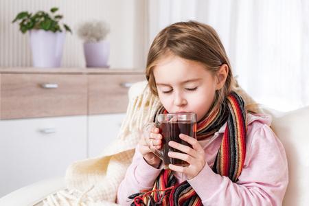 Bambina malata in sciarpa che beve il tè