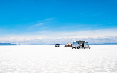Car with camping trailer and tent set up among sunshine Salar de Uyuni Stock Photo