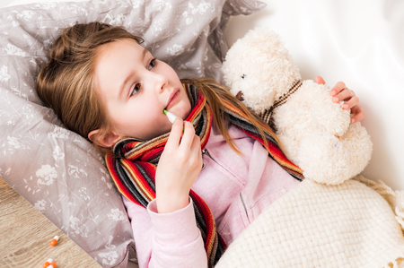 Little ill girl with bear measuring temperature