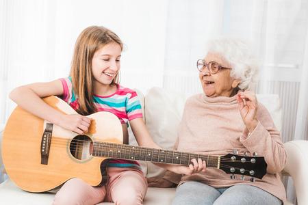 Grandmother listening granddaughter playing guitar
