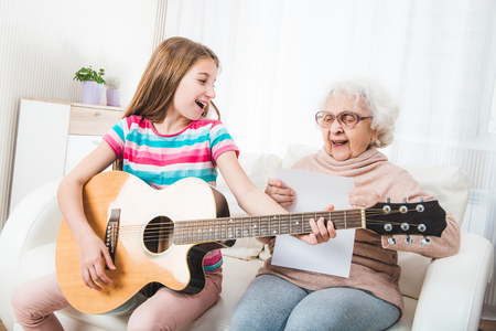 Smiling grandmother with granddaughter singing together with guitar
