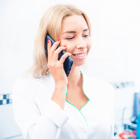Closeup of dental doctor in uniform talking on smartphone