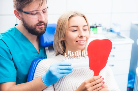 Dentist holding chosen teeth color and looking with girl in the mirror Фото со стока