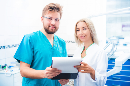 Dentists in uniform looking notes on notepad