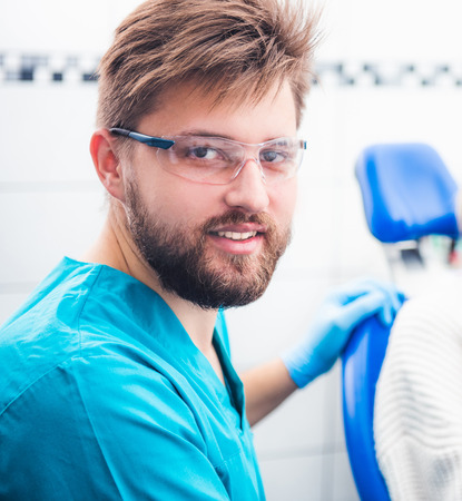 Smiling dentist with glasses and uniform in orthodental office