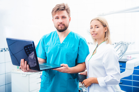 Dentists in uniform working with laptop